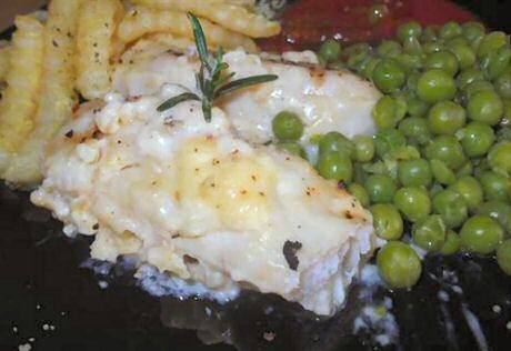 Vis in de oven klaargemaakt, geserveerd met erwtjes, friet, saus