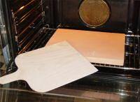 Pizzasteen en pizzaschep in een normale oven
