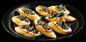 Tapenade gemaakt van fijn gesneden olijven, kappertjes, ansjovis, look, tijm, oregano met citroensap en olijfolie