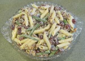 Koude pastasalade met penne, spek, olijven, druiven en prinsessebonen