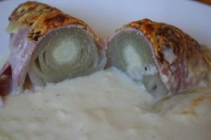 Gestoofd witloof opgerold in hespenrolletjes, gegratineerd met kaas in de oven en geserveerd met bechamelsaus